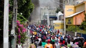 La gente camina en la calle durante las protestas por el aumento del precio del combustible en Puerto Príncipe, Haití.
