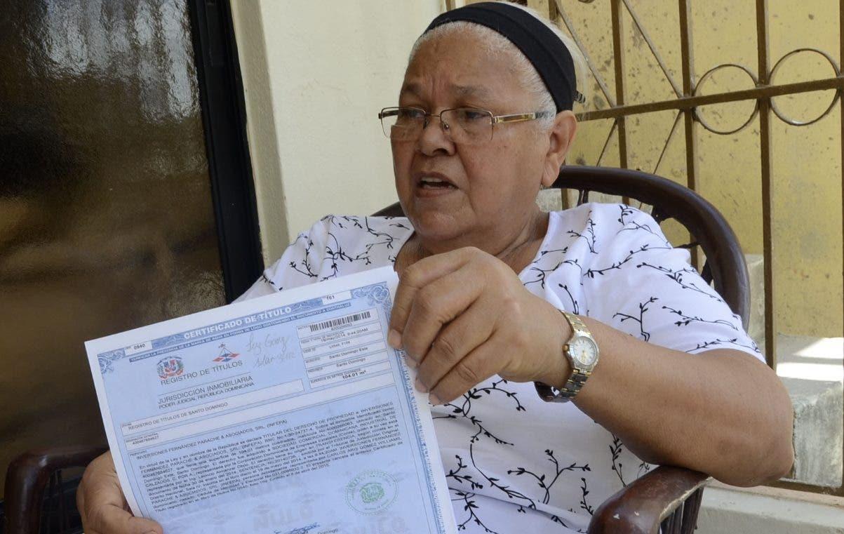 Luz Gómez, una de las estafadas, muestra el título que recibó tras pagar. JOSÉ DE LEÓN
