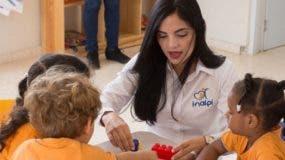 La directora del Inaipi,  Berlinesa Franco, junto a niños que reciben asistencia en un  centro.
