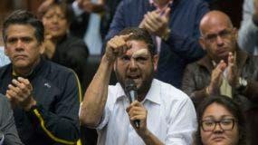 En esta foto de archivo del 5 de abril de 2017, el legislador opositor Juan Requesens, centro, que fue atacado por grupos pro gubernamentales, habla en la Asamblea Nacional durante una sesión en Caracas, Venezuela. (AP Foto / Ariana Cubillos, Archivo)