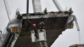 Bombero inspecciona el sitio del puente de la carretera Morandi colapsado en Génova, norte de Italia, el martes 14 de agosto de 2018. Una gran parte del puente se derrumbó sobre una zona industrial en la ciudad italiana de Génova durante una tormenta repentina y violenta, dejando a los vehículos aplastado en escombros a continuación. (Luca Zennaro / ANSA vía AP)