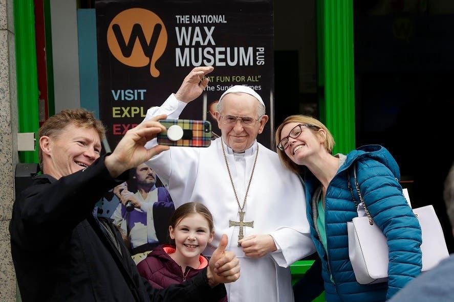 Una familia de irlandeses se hace fotos junto a una estatua del papa en una calle de Dublín.