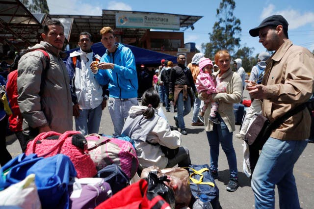 Venezuelan migrants stand in line to register their exit from Colombia before entering Ecuador at the Rumichaca International Bridge