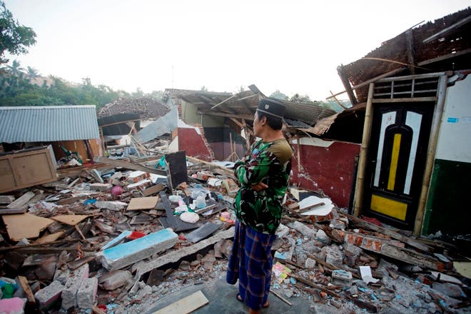 Un hombre inspecciona las ruinas de su casa, destruida por un sismo en Lombok Norte, Indonesia. AP