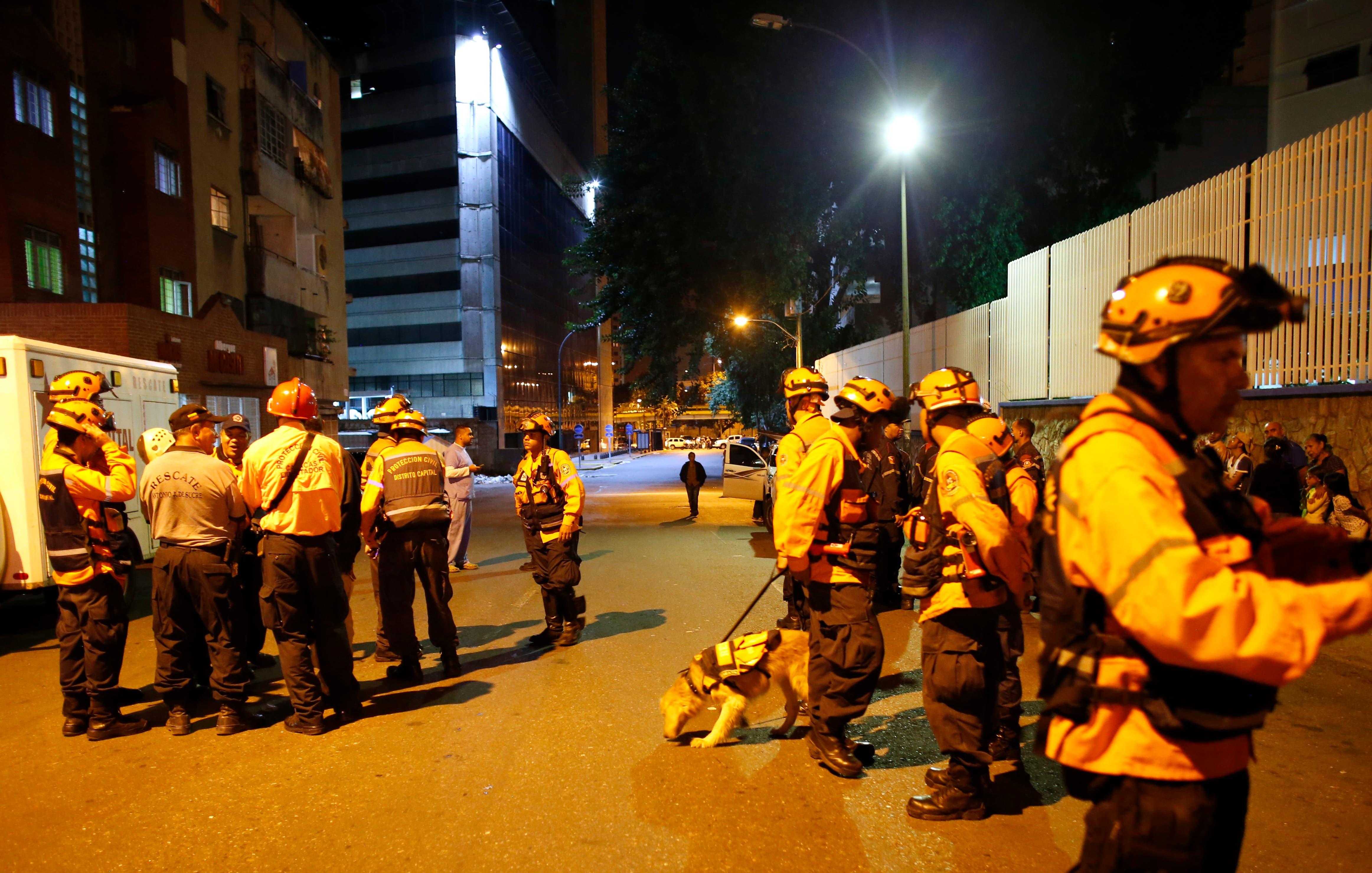 """Los trabajadores de Protección Civil patrullan cerca del rascacielos """"Torre de David"""", que sufrió una inclinación después de que un poderoso terremoto sacudiera el este de Venezuela, causando la evacuación de edificios en la capital de Caracas, Venezuela, el martes 21 de agosto de 2018. AP"""