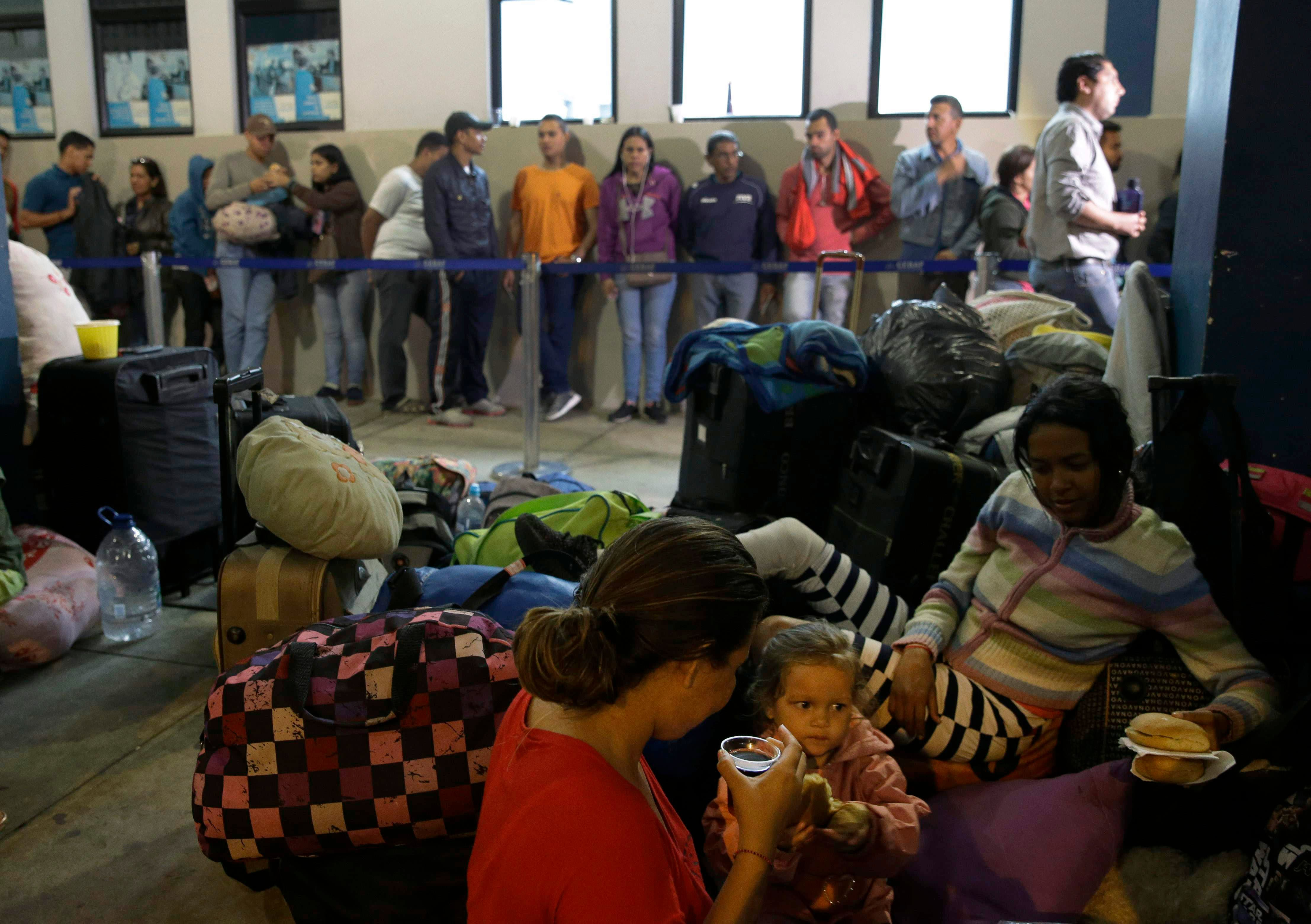 Los migrantes venezolanos descansan mientras otro grupo hace fila para ingresar a la oficina de inmigración en Tumbes, Perú, el sábado 25 de agosto de 2018. Miles de venezolanos cruzan hacia Perú horas antes de que las autoridades comiencen a aplicar normas más estrictas que harán que ingresar al país sudamericano sea más difícil. (AP Photo / Martin Mejia)