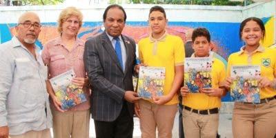 Enrique Lacoste, Rosa García Crespo y Jorge Zorrilla entregan la historieta a estudiantes en Puerto Plata.