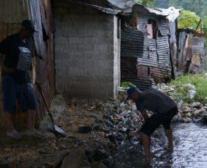 Moradores de la Ciénega sacan basura arrastrada por el río.