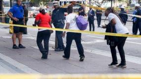 Efectivos de seguridad permiten que unas personas evacúen una zona acordonada luego que ocurriera un tiroteo cerca de Fountain Square, en el centro de Cincinnati, el jueves 6 de septiembre del 2018. (Foto AP /John Minchillo)