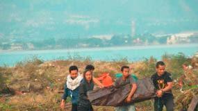 Las personas llevan el cuerpo de una víctima del tsunami en Palu, Sulawesi Central, Indonesia. AP