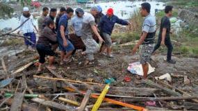 Habitantes de la localidad cargan en una bolsa el cadáver de una víctima del tsunami en Palu, en la provincia indonesia de Célebes. (AP Foto)