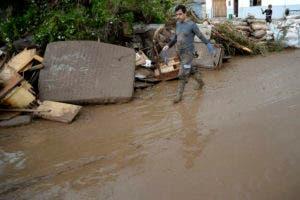 Un hombre pasa junto a los muebles dañados después de las inundaciones, en Sant Llorenc, a 60 kilómetros (40 millas) al este de la capital de Mallorca, Palma, España. AP