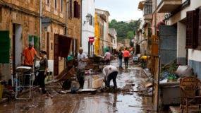 Residentes limpian el lodo de las calles inundadas en Sant Llorenc, a 60 kilómetros (40 millas) al este de la capital de Mallorca, Palma, España, el miércoles 10 de octubre de 2018. (AP Foto/Francisco Ubilla)
