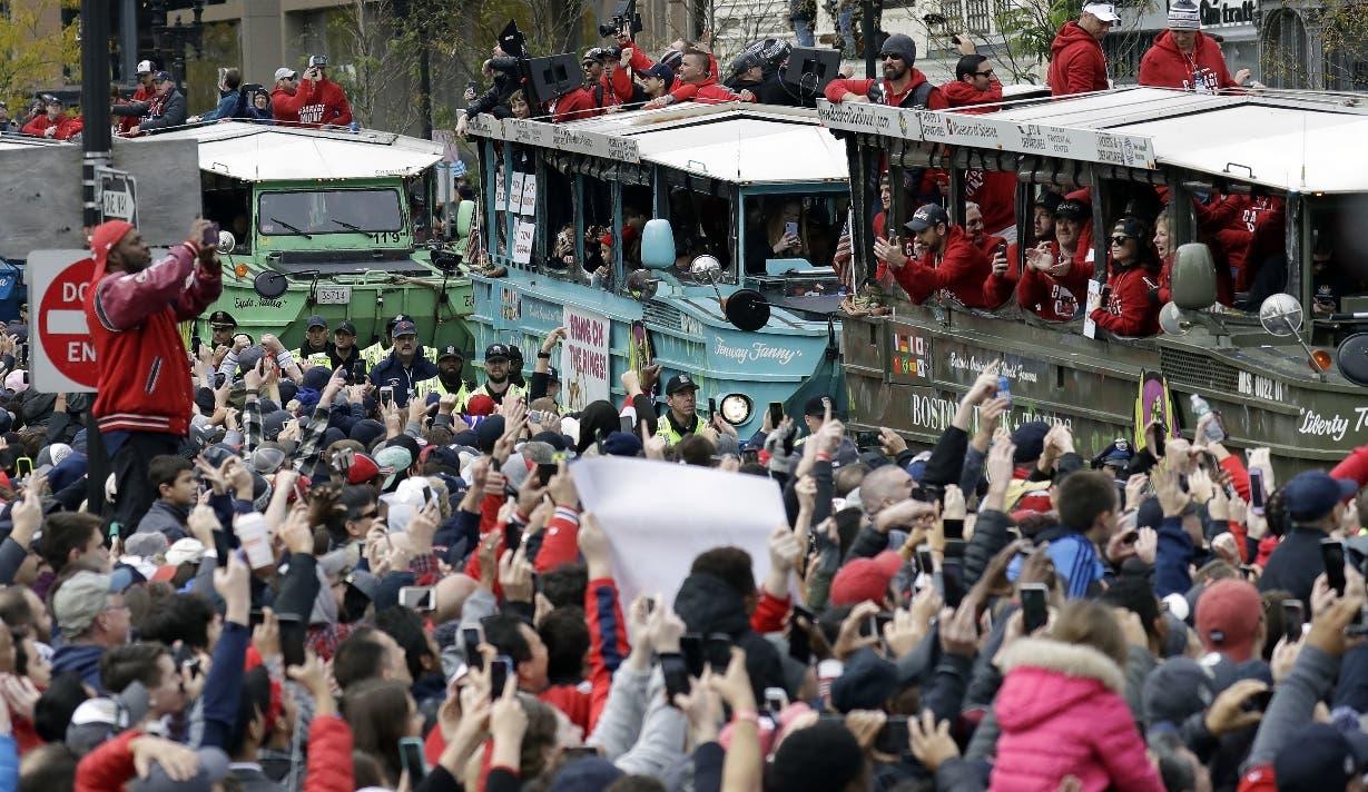 Aficionados saludan a los jugadores de los Medias Rojas durante el desfile de la victoria. AP