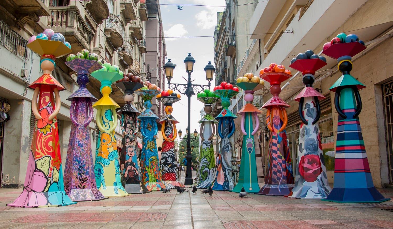 La exposición 12 esculturas de 11 pies de altura de muñecas sin rostros y jardineras con flores trinitarias que embellecen la calle El Conde.
