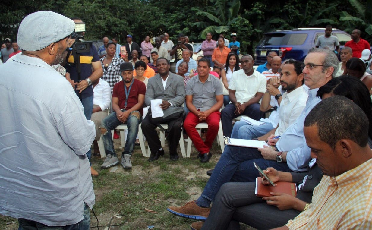 Luis Abinader escucha a un dirigente comunitario durante un encuentro con simpatizantes.