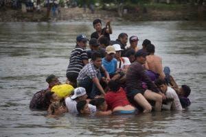 Migrantes cruzando un río entre Guatemala y México. (AP Photo/Moises Castillo)