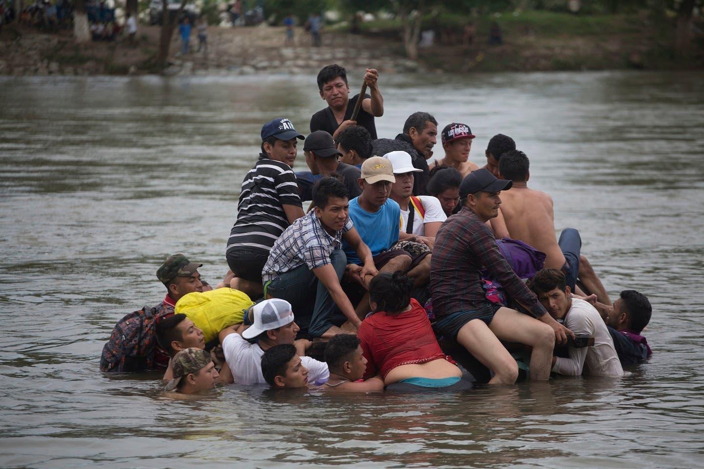 12. Migrantes cruzando un río entre Guatemala y México. (AP Photo/Moises Castillo)