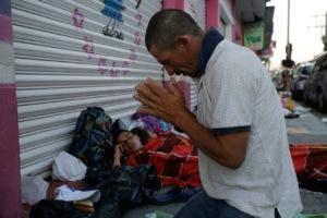 Marvin Sanabria, uno de los cientos de migrantes que  participa en la caravana, reza después de dormir a la intemperie. (AP Photo/Moises Castillo)