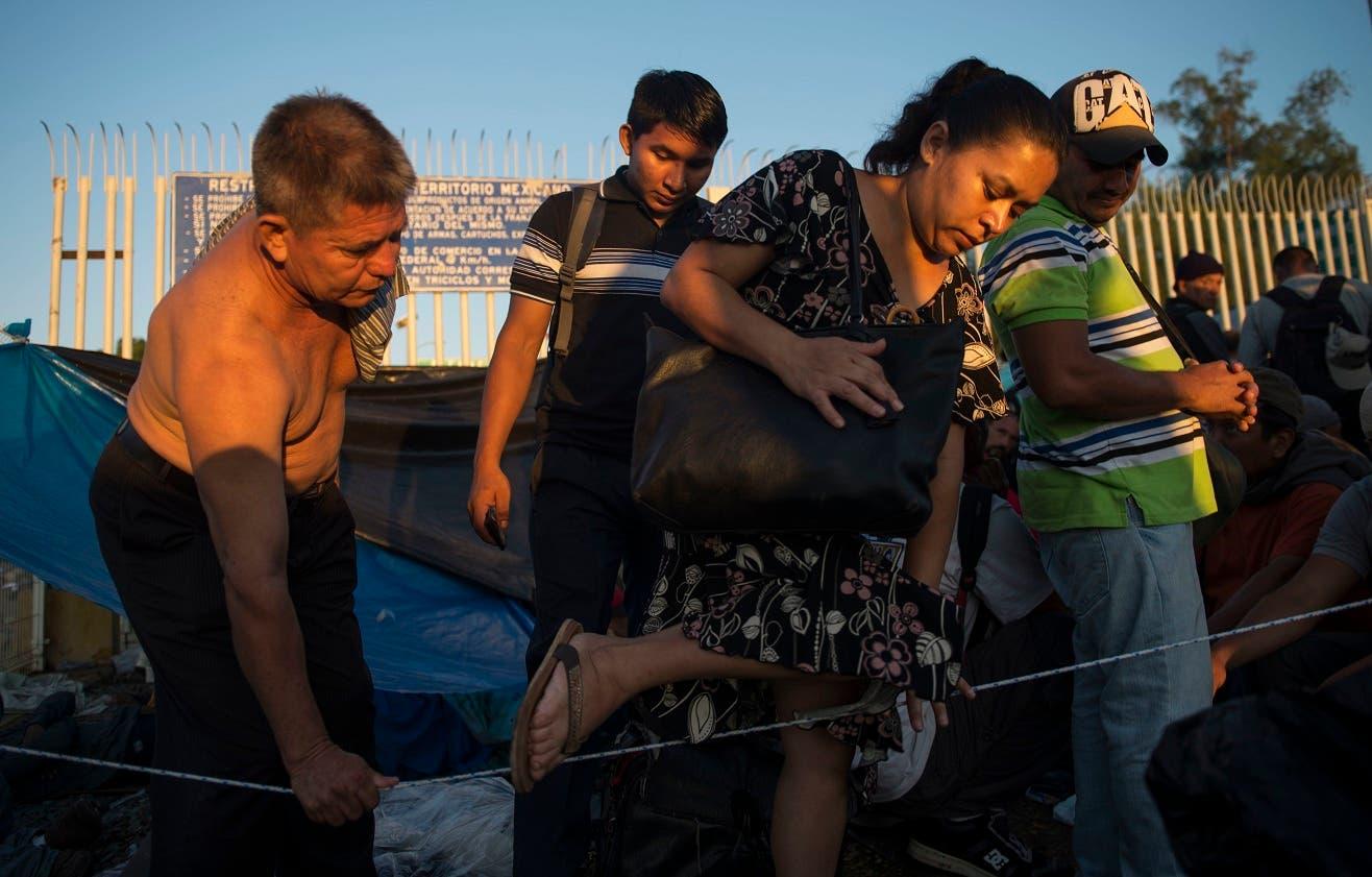 5. Un hombre ayuda a otra migrante a cruzar de una sección a otra cuando centroamericanos se organizan en bloques  para ser asistidos por las autoridades de inmigración en México, en el puente sobre el río Suchiate, que conecta Guatemala con México, el Tecun Uman, Guatemala, el lunes, 22 de octubre del 2018. (AP Foto/Oliver de Ros)