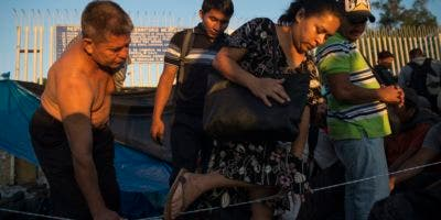 Un hombre ayuda a otra migrante a cruzar de una sección a otra cuando centroamericanos se organizan en bloques  para ser asistidos por las autoridades de inmigración en México, en el puente sobre el río Suchiate, que conecta Guatemala con México, el Tecun Uman, Guatemala, el lunes, 22 de octubre del 2018. (AP Foto/Oliver de Ros)