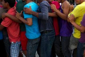 Los migrantes luchan por mantener el orden mientras esperan en la fila para recibir alimentos donados en San Pedro Tapanatepec, en el estado de Oaxaca, México, el domingo 28 de octubre de 2018.  (AP Foto / Rebecca Blackwell)