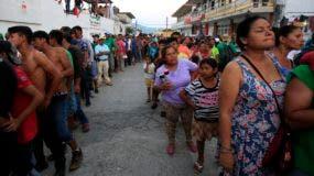 Los migrantes esperan en fila para recibir alimentos donados, mientras una caravana de centroamericanos que intentan llegar a la frontera con Estados Unidos se detiene en un día de descanso en Tapanatepec, México, el domingo 28 de octubre de 2018. (AP Foto / Rebecca Blackwell)