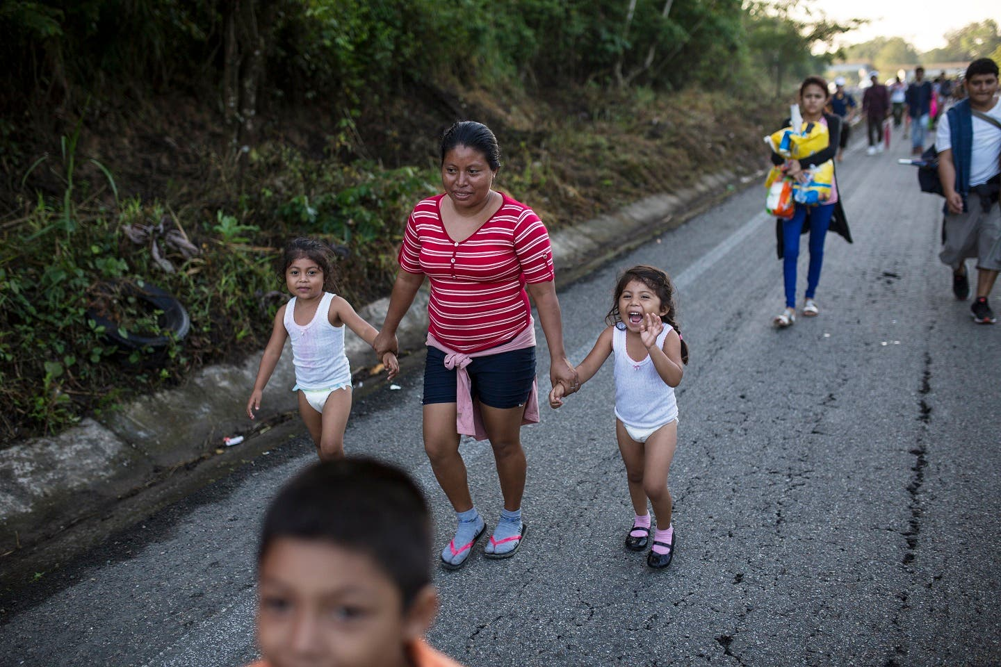 2. Silvia camina junto a sus hijas  Karen, 5, , and Beiyi, 4, with a caravan to the U.S., make their way to Mapastepec, Mexico, Wednesday, Oct. 24, 2018. Thousands of Central American migrants renewed their hoped-for march to the United States on Wednesday, setting out before dawn with plans to travel another 45 miles (75 kilometers) of the more than 1,000 miles that still lie before them. (AP Photo/Rodrigo Abd)