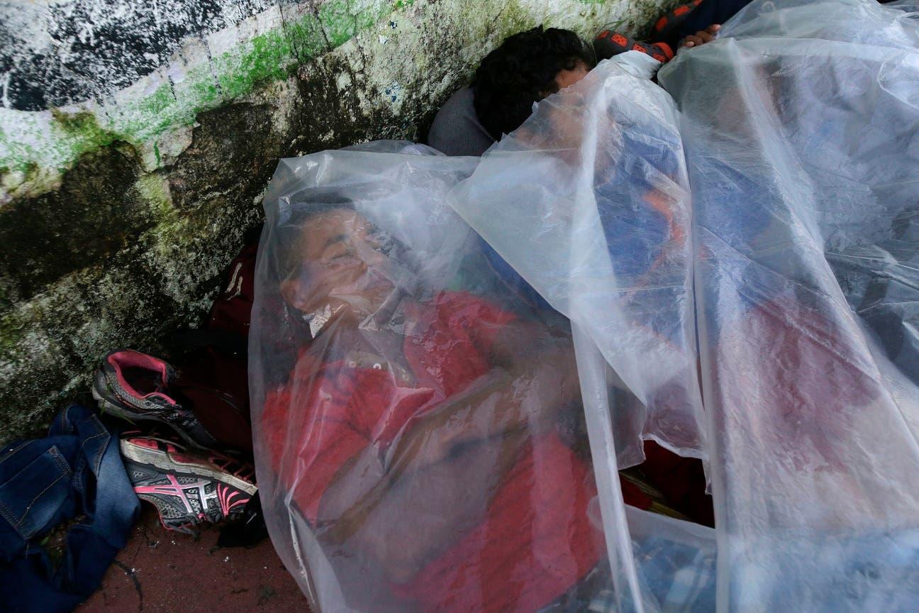 22. Migrantes centroamericanos que viajan en caravana hacia Estados Unidos duermen cubiertos con bolsas de plástico en una vereda de Huixtla, México, al martes 23 de octubre del 2018. (AP Foto/Moisés Castillo)