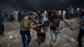 Manifestantes palestinos evacúan a uno de sus compañeros heridos por soldados israelíes durante una protesta en la Franja de Gaza.