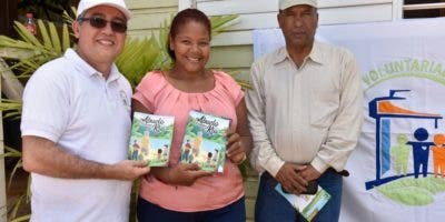 Luis Martín Gómez y Onofre Rojas entregan ejemplares del cuento a Dulce María Peralta, directora de la Escuela Pepe Pérez, de Yamasá, Monte Plata.