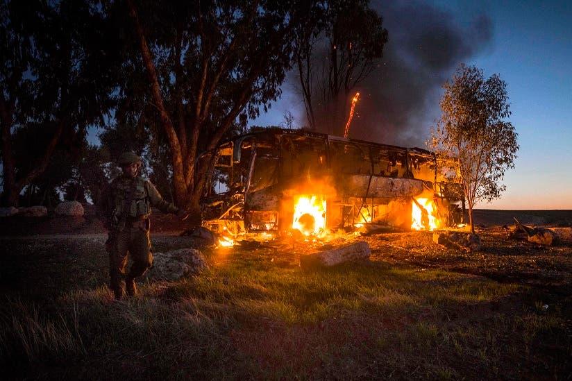 Un soldados israelí, junto a un autobús en llamas tras ser alcanzado por una bomba de mortero lanzada desde Gaza, cerca de la frontera con Israel, el 12 de noviembre de 2018. (AP Foto/Tsafrir Abayov)