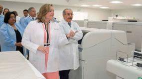Patricia León muestra los equipos al presidente Medina y otros funcionarios.