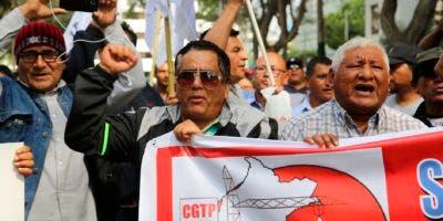 Miembros de los sindicatos de la construcción protestan contra Alan García frente a la embajada de Uruguay en Lima, donde está el expresidente.