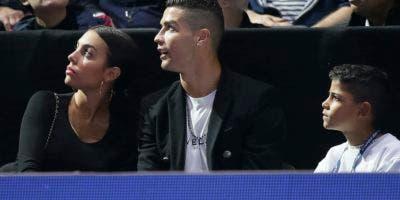 Cristiano Ronaldo, centro, con su pareja Georgina Rodriguez, y su hijo Cristiano Ronaldo Jr. observan un partido de tenis entre Novak Djokovic y John Isner en London (AP Photo/Tim Ireland).
