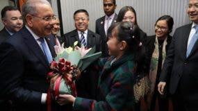 Danilo Medina recibe flores de manos de una niña  a su llegada a Beijing.