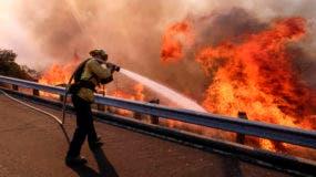 Un bombero combate un siniestro al lado de la autopista Ronald Reagan, o carretera estatal 118, en Simi Valley, California. (AP Foto/Ringo H.W. Chiu)