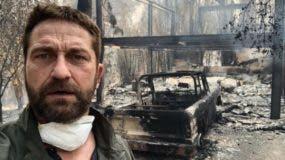 El actor Gerard Butler (  de la película 300) posa frente a los restos calcinados de su propiedad.