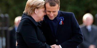 El presidente francés Emmanuel Macron, a la derecha, toma las manos de la canciller alemana, Angela Merkel, durante una ceremonia en Compiegne, al norte de París. (AP Photo/Michel Euler)