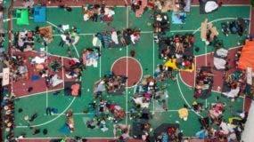 De camino a Estados Unidos, un grupo de migrantes para pasar la noche en una cancha de básquetbol en México.