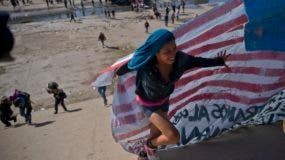 Un grupo de migrantes cruza el lecho de un río en la frontera con Estados Unidos tras superar a unos policías mexicanos en Tijuana, México, el domingo 25 de noviembre de 2018. (AP Foto/Ramón Espinosa)