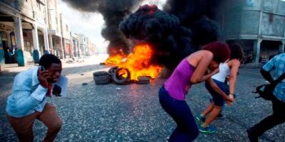 La gente corre después de quemar neumáticos durante una protesta para exigir saber cómo los fondos de Petro Caribe han sido utilizados por el presente y el pasado. AP