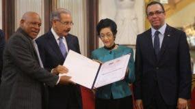 El presidente Danilo Medina entrega el reconocimiento a  María del Carmen -Carmenchu- Brusiloff. Les acompañan: Adriano de la Cruz y Andrés Navarro.