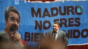 """Un legislador pasa junto a una pancarta que dice: """"(Nicolás) Maduro, no son bienvenidos"""" pegados a la pared en la cámara baja del Congreso, solo un par de nuestros antes de que el líder venezolano esté programado para asistir a la toma de posesión del Presidente electo. AP"""