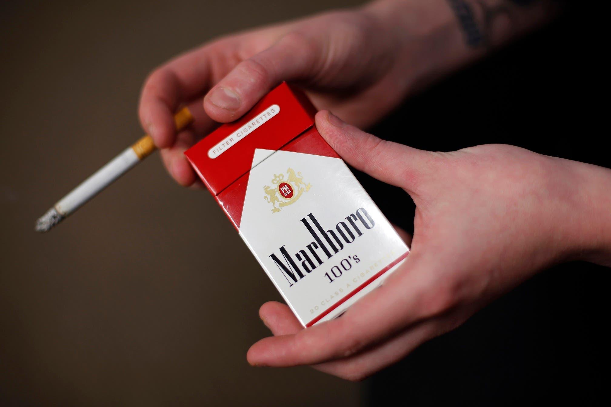 Fotografía de archivo del 17 de julio de 2015 de la administradora de tienda Stephanie Hunt posando con un paquete de cigarrillos Marlboro en la tienda Smoker Friendly en Pittsburgh. (AP Foto/Gene J. Puskar, Archivo)