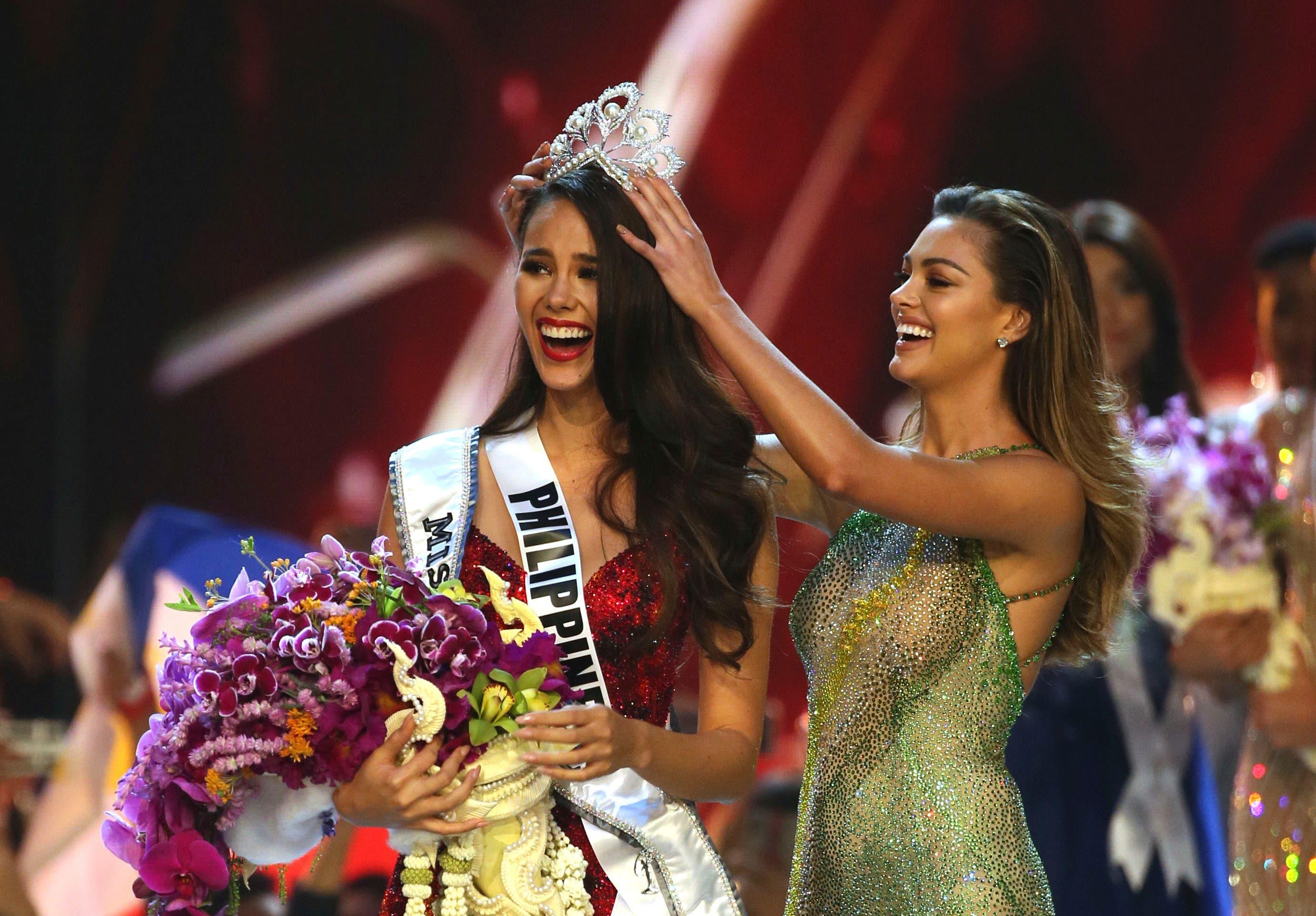 2. Catriona Gray de Filipinas, izquierda, sonríe al recibir la corona de Miss Universo 2018  de manos de Miss Universo Demi-Leigh Nel-Peters durante la final de la 67ma edición de Miss Universo en Bangkok, Tailandia, el 17 de diciembre de 2018. (Foto AP/Gemunu Amarasinghe)