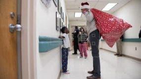 Obama entrega regalos a niños enfermos vestido con gorro y saco de Papa Noel. EFE