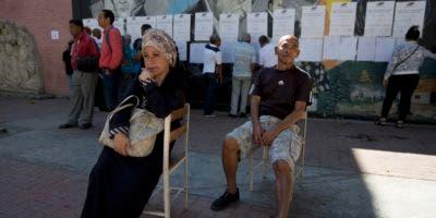 Los votantes esperan para depositar sus boletas mientras otros miran las listas de sus mesas de votación durante las elecciones locales en Caracas, Venezuela, el domingo 9 de diciembre de 2018. Los venezolanos acuden a las urnas Delitos y amenazas de expulsión por parte de los grupos de oposición. (Foto AP / Fernando Llano)