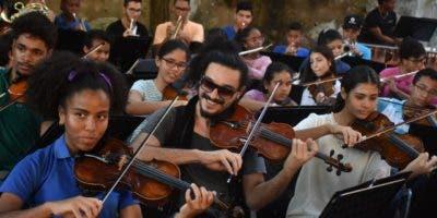 El violinista Nemanja Radulovic con gafas de sol, ensaya junto a los niños de la Fundación Fiesta Clásica.