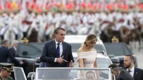 Acompañado por la primera dama Michelle Bolsonaro, el presidente de Brasil, Jair Bolsonaro, hace una señal con sus dedos índices mientras se desplaza en un auto abierto después de su ceremonia de investidura el martes 1 de enero de 2019 en Brasilia. (Foto AP/André Penner)
